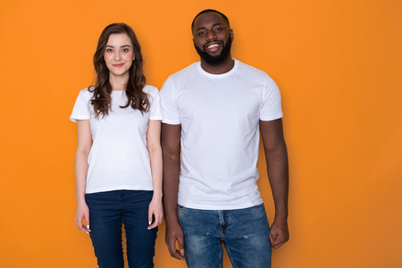 Beautiful interracial couple in white T-shirts posing for camera
