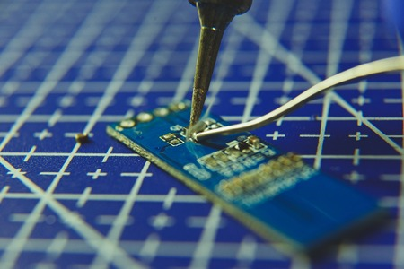 Close up of soldering iron and microchip on blue background
