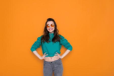 Waist up of attractive fashionable Caucasian girl wearing stylish eyeglasses in studio