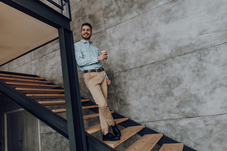 Cheerful young man is enjoying coffee on steps