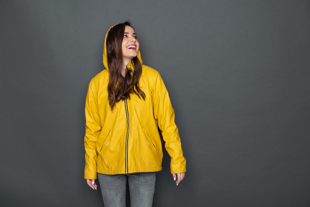 Cropped photo of happy Caucasian girl wearing yellow raincoat against gray background Stockfoto