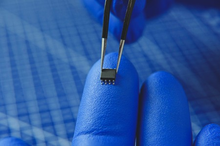 Cropped photo of man keeping microchip with tweezers on finger Standard-Bild