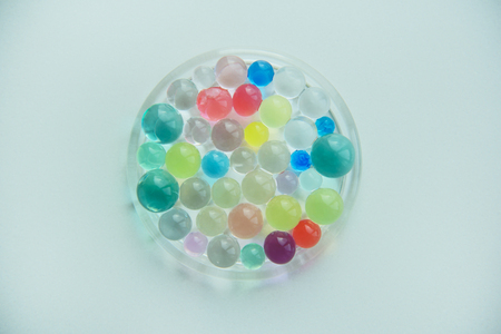 Plate with colorful hydrogel balls isolated on white background