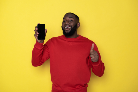 Waist up of smiling African man holding smartphone in arms