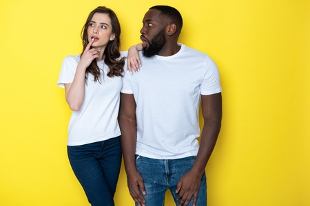 Young interracial couple in white T-shirts posing for camera in studio