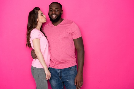 Waist up of happy interracial couple posing for camera in studio
