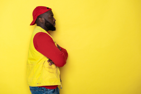 Side view of bearded African man with crossed hands against yellow background Фото со стока