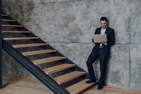 Smiling businessman is using laptop at staircase indoors