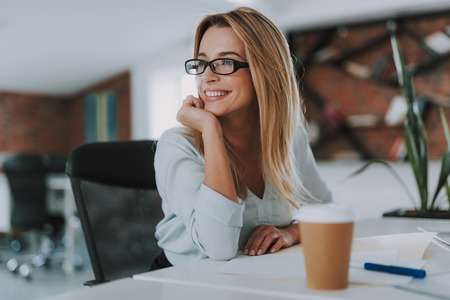 Happy woman in glasses smiling and looking into the distance