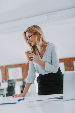 Waist up of the positive woman drinking coffee in her office