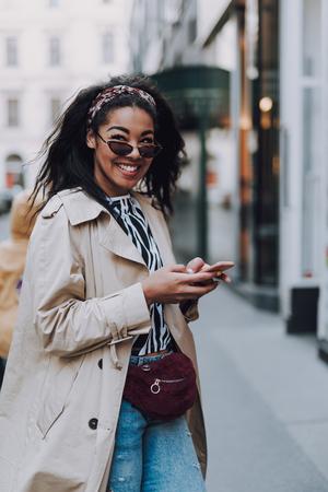 Charmantes afroamerikanisches Mädchen mit Handy auf der Straße Standard-Bild