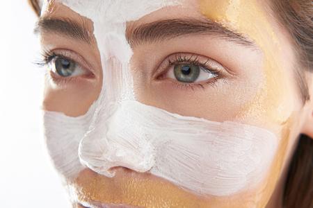 Faccia superiore di bella donna con maschera cosmetica