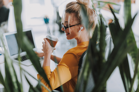Woman with plants by her side drinking coffee and smiling