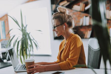 Femme souriante touchant une tasse de café sur la table tout en travaillant