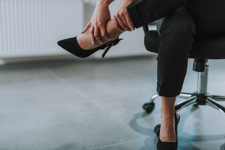 Woman touching her leg after tiresome working day