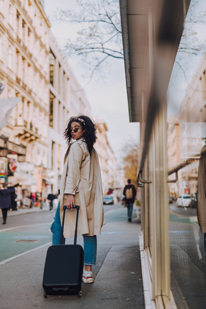 Charming afro american girl with travel trolley bag standing on the street Stock Photo