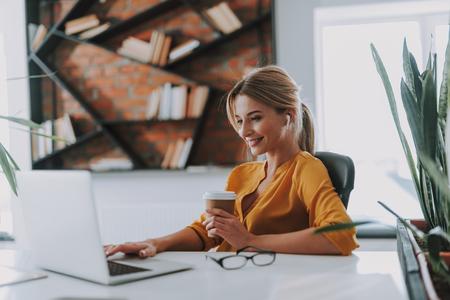 Positive businesswoman in her office working on the laptop Reklamní fotografie