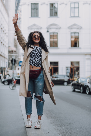 Attractive afro american girl showing hello gesture on the street