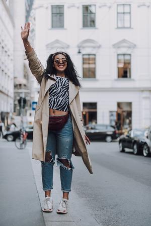 Attraente ragazza afroamericana che mostra un gesto di saluto per strada Archivio Fotografico