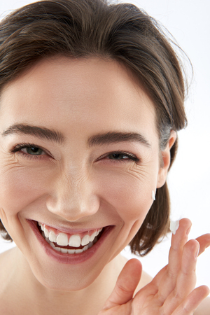 Happy female with drop of cream on finger Stock Photo