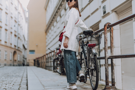 Beautiful young woman with bicycle standing on the street