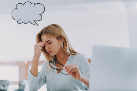 Woman touching her nose and closing eyes after working