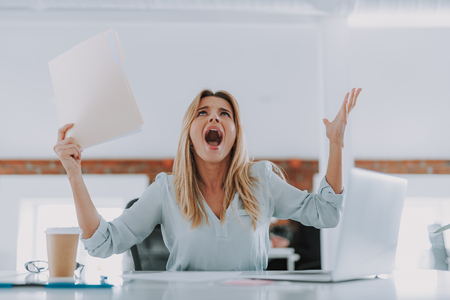 Young woman throwing hands up in anger and irritation Stock Photo
