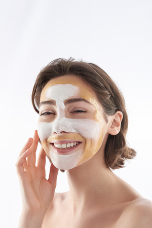 Portrait of happy woman with cosmetic mask