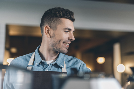 Close up of smiling barista at his workplace alone