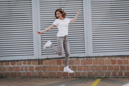 Happy young hipster girl jumping up on city view Stock fotó