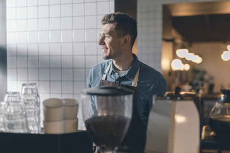 Positive barista looking glad while being at work