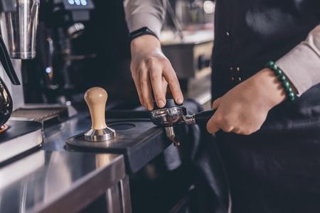 Careful barista pressing coffee in filter holder