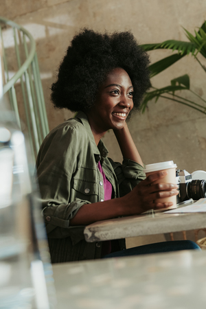 Waist up of cheerful young African woman having rest in cafeteria