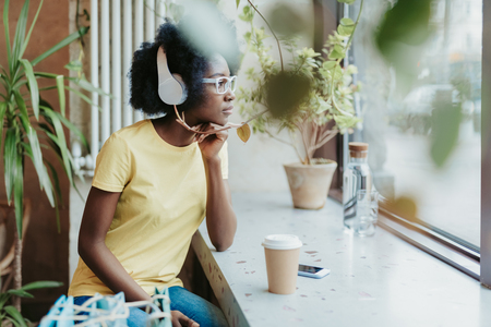 Waist up of African lady wearing casual and having rest in cafe Stock Photo - 122925839