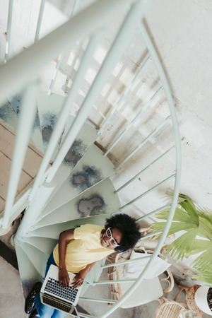 Cropped photo of African woman working on digital gadget indoors 版權商用圖片