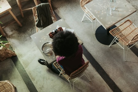 Busy African woman with curly hair taking photos in cafeteria Imagens