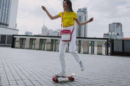 Happy smiling hipster girl skating on penny board
