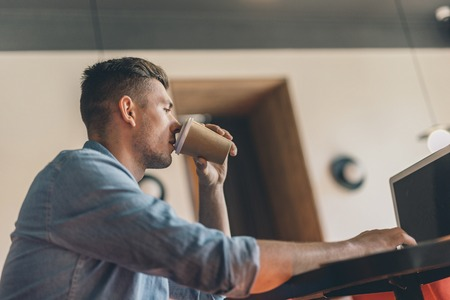 Thoughtful young man drinking coffee and looking at the screen