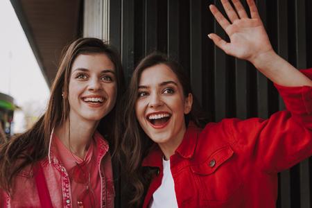 Dos chicas hipster felices saludando a alguien