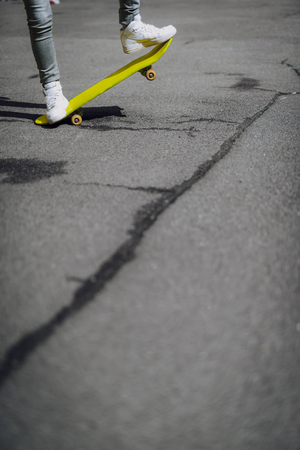Hipster girl legs balancing on yellow skateboard