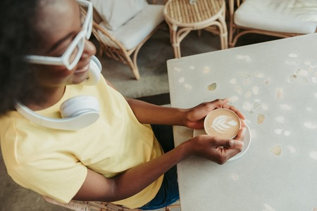 Cropped photo of African woman having rest and drinking coffee in cafeteria Stockfoto