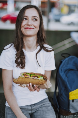 Smiling female sitting outdoor with hot dog