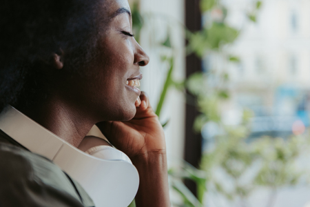 Side view of happy African woman with headphones on shoulders having rest