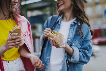 Two happy female friends eating hot dogs by walk