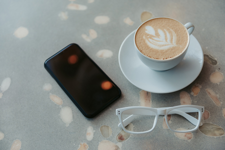 Cup of coffee, glasses and smartphone lying on table Stockfoto
