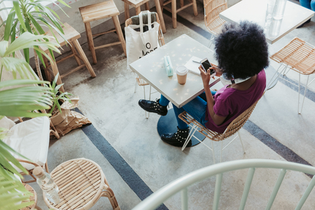 High angle of African woman looking at screen of mobile phone
