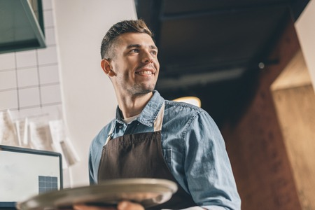 Smiling waiter with tray looking into the distance