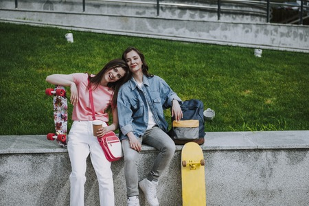 Two pretty skater girls relax after skateboarding 版權商用圖片