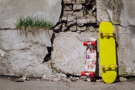Two colorful skateboard leaning on cracked wall