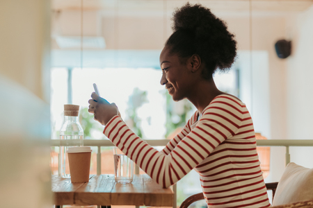 Low angle of happy African woman having rest in cafe